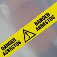 Asbestos warning sign on yellow tape