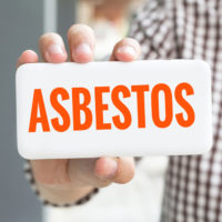 Man holding asbestos sign