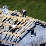 construction workers building a roof of a house