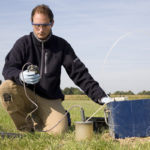 Researcher taking samples from groundwater for environmental research.