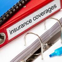 large red folder for insurance coverages including blue ring binder and blue marker