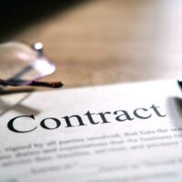 Contract sheet with glasses and a pen on a wooden background