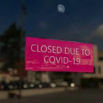 "Close-up on a closed sign in the window of a shop displaying the message ""Closed due to Covid-19"". The glass reflects the day city"