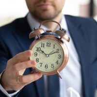 Close up of businessman hold clock showing time limit