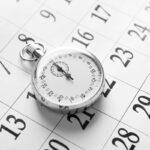 Stopwatch on calendar background, close up